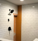 white subway tile shower with hardware installed