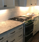 white subway tile installed and stainless steel range