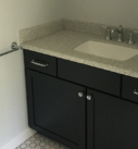 black painted wood bathroom vanity with gray and white countertop