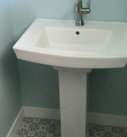 white pedestal sink with green and white tile flooring