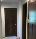 hallway of dark stained 3 panel doors